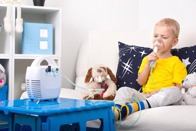 吸入器を使う男の子とぬいぐるみの犬