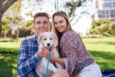 犬を可愛がっているカップル