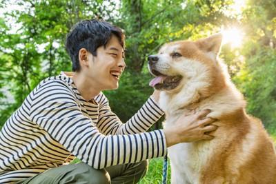 笑顔の男性に撫でられている犬