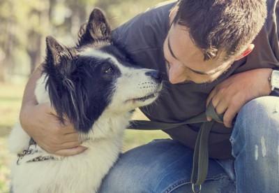 飼い主さんと顔を寄せ合う犬