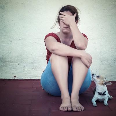 頭を抱える女性と寄り添う犬