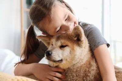 犬の顔に顔を寄せる女の子