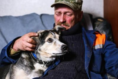 年配の男性に寄り添う犬