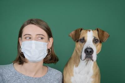 マスクを着けた女性と犬