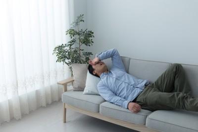 ソファに横たわって眠そうな男性