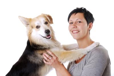 女性に前足をかける犬