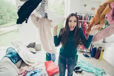 散らかった部屋で洋服を投げる女性