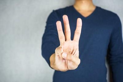 指を3本立てた人の手
