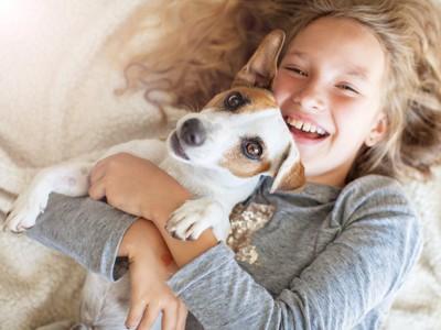 ベッドで犬を抱きしめる女の子