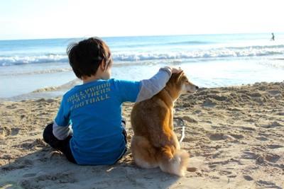 海で座る犬と子ども