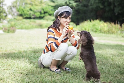 ボールで犬と一緒に遊ぶ女性