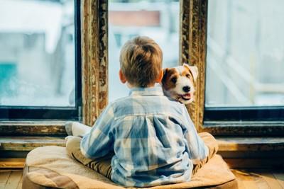座っている男の子と犬