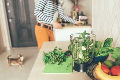 キッチンで野菜ジュースを作る女性と犬