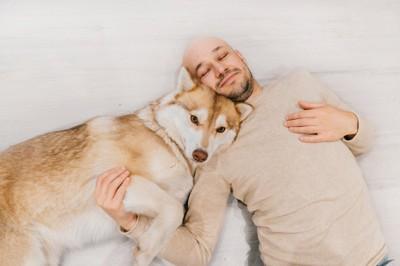 寝そべる男性とハスキー犬