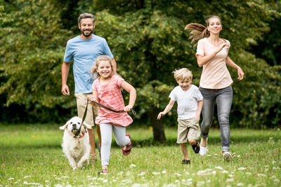 散歩中に走る犬と家族