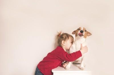抱きついてくる子供に引いている犬