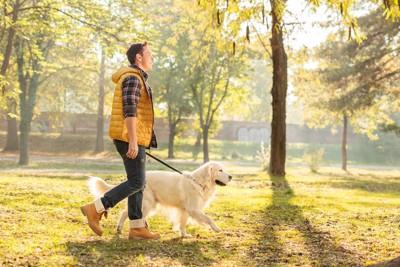 男性と歩く犬