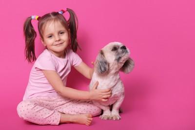 ピンクの服を着た少女とそっぽを向く犬