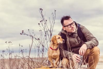 同じ方向を見つめる男性と犬