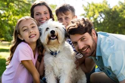 犬を囲む笑顔の家族