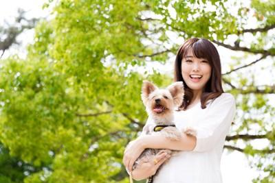 緑を背景に抱っこされる犬と女性