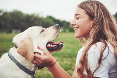 笑顔で顔を見合わせる女性と犬