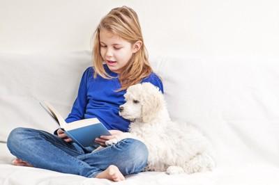 女の子と一緒に本を読んでいる犬