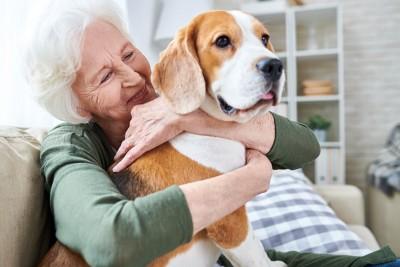 ソファーで犬を抱きしめるおばあさん