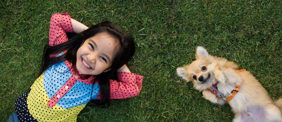 並んで仰向けに寝る女の子と犬