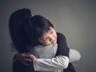 母親に抱きついて甘える男の子