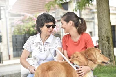 二人の女性と白いハーネスを着けた犬