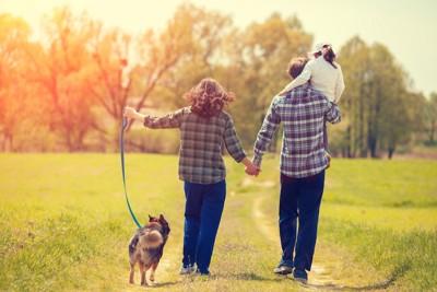 家族三人と散歩をする犬