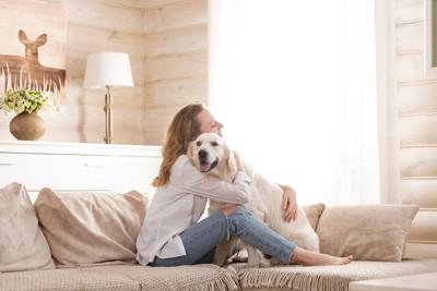 ソファーで犬を抱きしめる女性
