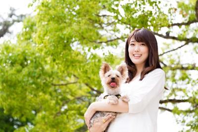 緑の中で犬を抱く女性
