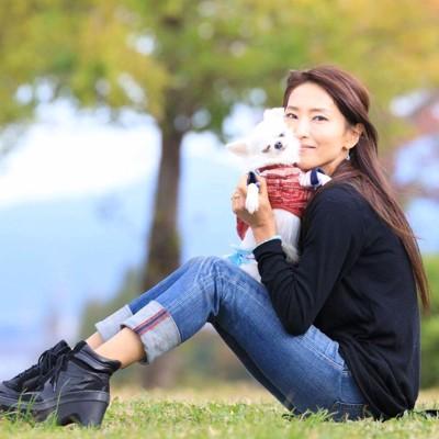 小型犬を抱っこして座っている女性