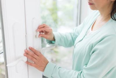 家の戸締まりをする女性