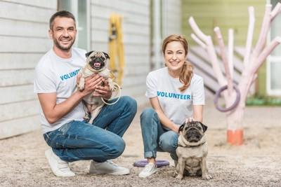 ボランティアの男女と犬
