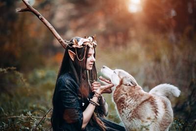 森の中で見つめ合う女性と犬