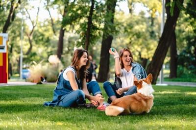 芝生に座る2名の女性と犬の後姿