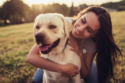 愛犬を後ろから抱きしめる女性