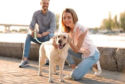 犬を連れた男性と犬を撫でる女性