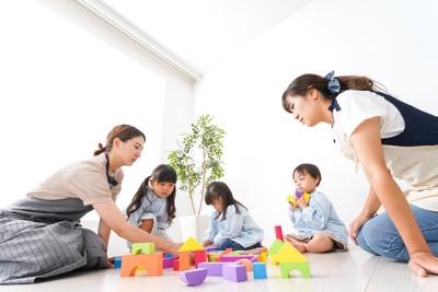 積み木で遊んでいる子どもたちと母親たち