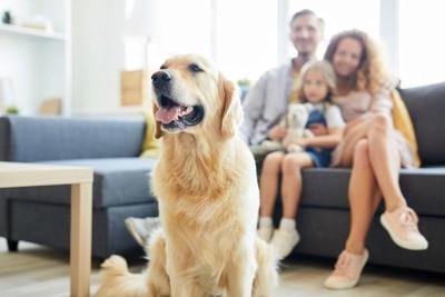 ソファーに座る家族と笑顔の犬