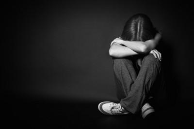 膝を抱えて泣く女性