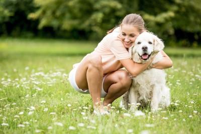 笑顔の女性に抱きしめられる犬