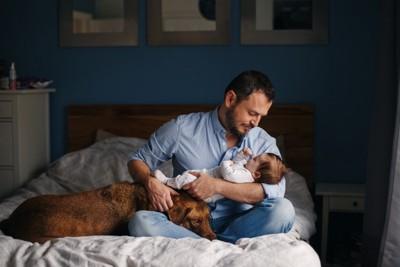 赤ちゃんを抱く父親と寄り添う犬