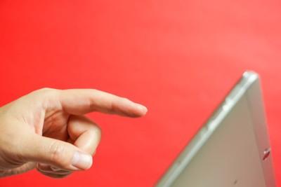 タブレットを操作する指