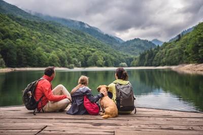 水辺に座る犬と家族の後ろ姿