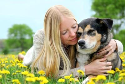 飼い主に抱きしめられる犬