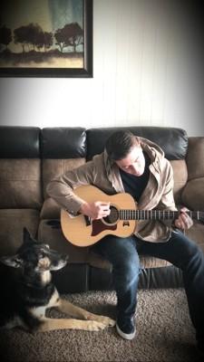 ギターを弾いてる男性と犬
